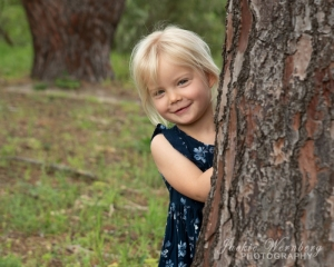 Little- girl- peeping- around- tree