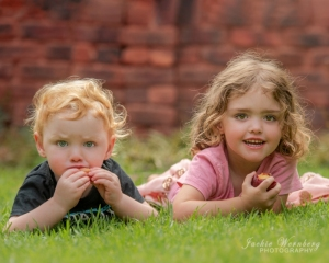brother-and-sister-lying-on-tummies-on-grass