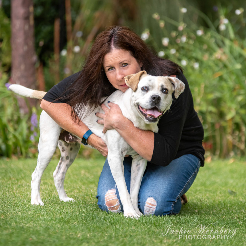 White Pitbull being hugged by woman
