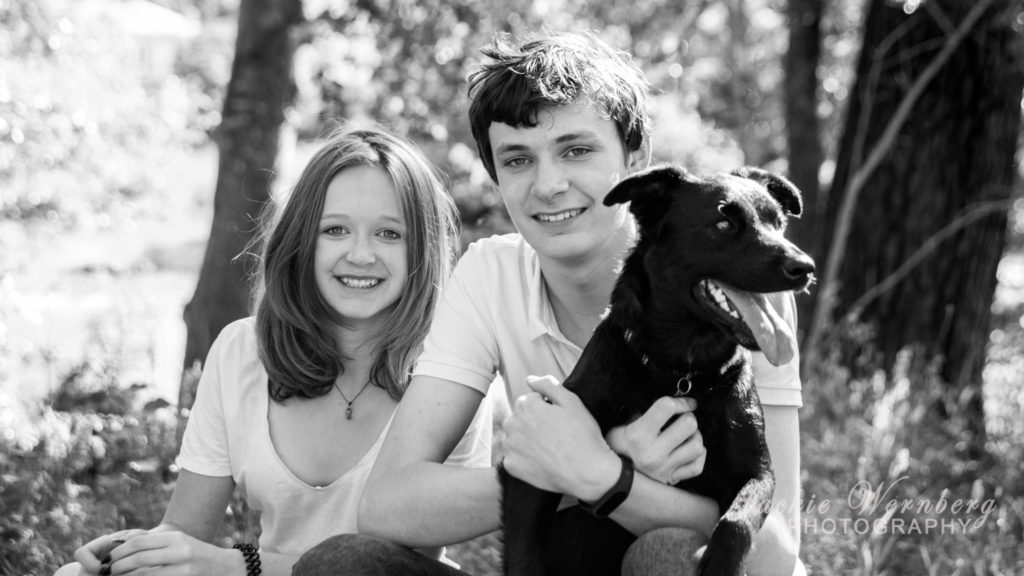 brother and sister in park with black dog